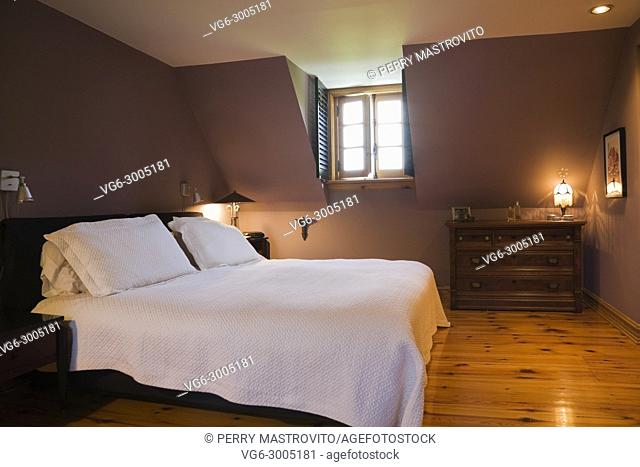 Bed and antique wooden dresser in the master bedroom on the upsatirs floor inside a stacked log home, Monteregie, Quebec, Canada