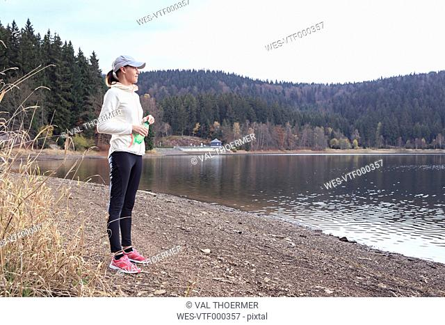 Female jogger with water bottle standing at lakeshore enjoying view