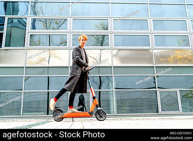 Man riding electric push scooter on footpath by building