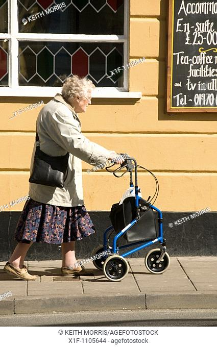 Old elderly woman walking on street with mobility aid - three wheeler shopping buggy