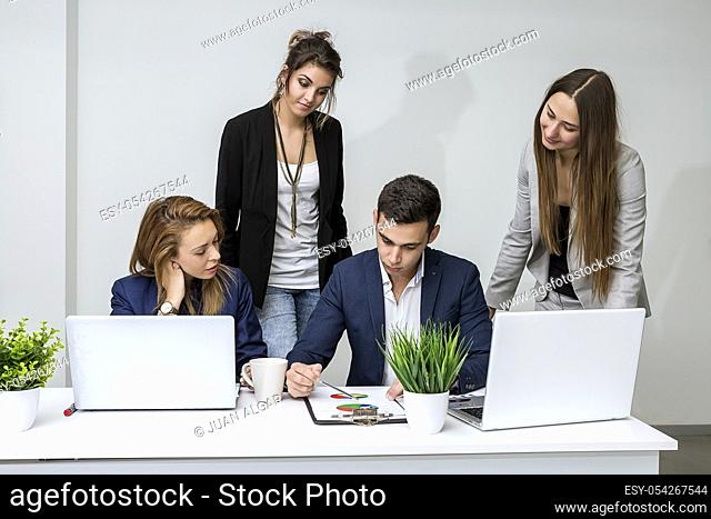 The group of managers sitting and browsing the diagram in the office. Horizontal indoors shot