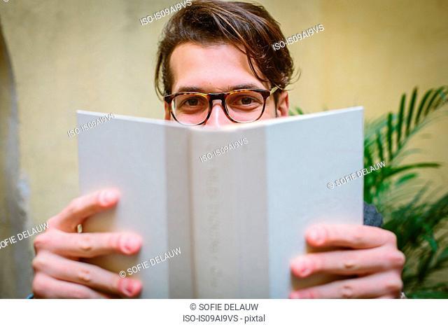 Man half-hiding behind book