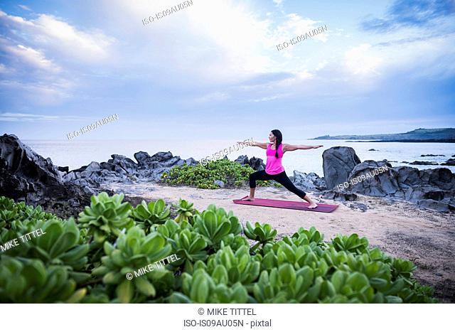 Woman practicing warrior yoga pose on beach, Hawea Point, Maui, Hawaii, USA