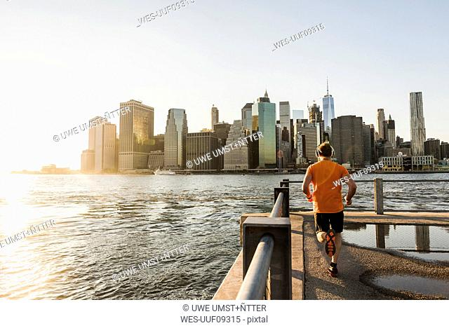 USA, Brooklyn, back view of man jogging in front of Manhattan skyline in the evening