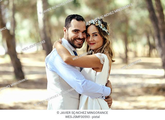 Portrait of happy bridal couple standing head to head in pine forest