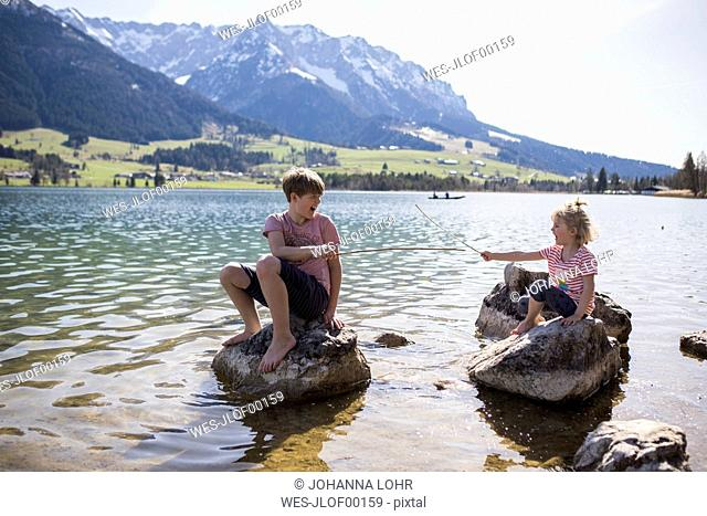 Austria, Tyrol, Walchsee, brother and sister sitting on boulders in the lake playing with sticks
