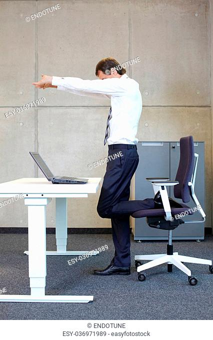 exercises in office. business man taking short break for stretching in standing position