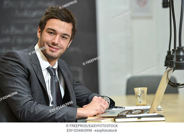 Portrait of smiling Businessman posing in modern office