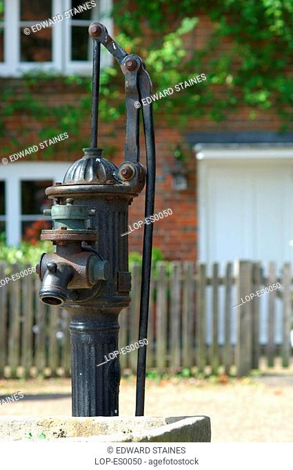 England, Buckinghamshire, Hambleden, Old water pump with cottage in background at Hambleden Village. The name is Anglo Saxon in origin and means 'crooked or...