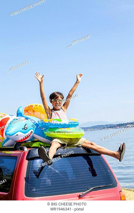 Child poses beach toys and floaties on the roof of a car