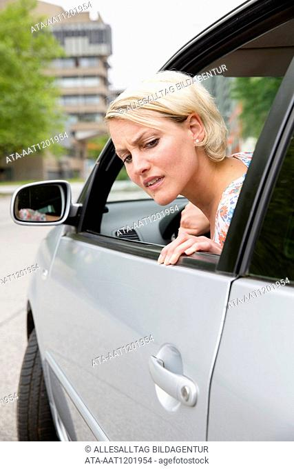 Female car driver parks her car