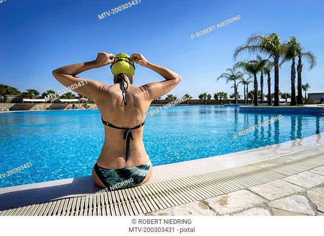 Rear view of mature woman sitting at poolside and wearing swimming cap, Puglia, Italy