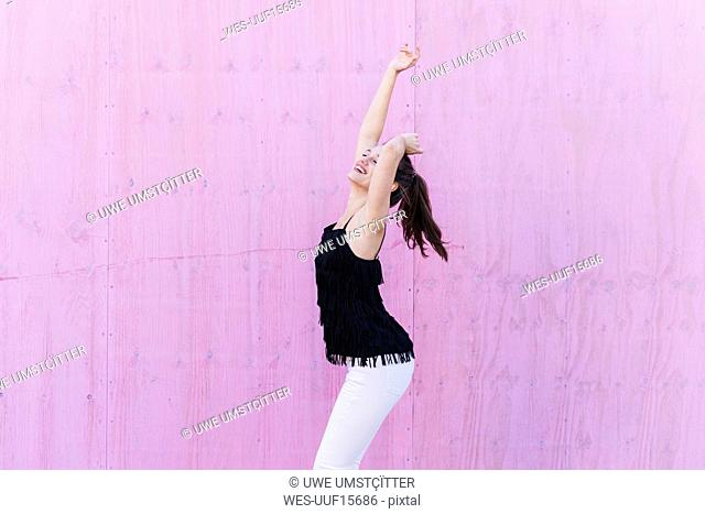Happy young woman standing in front of pink wall