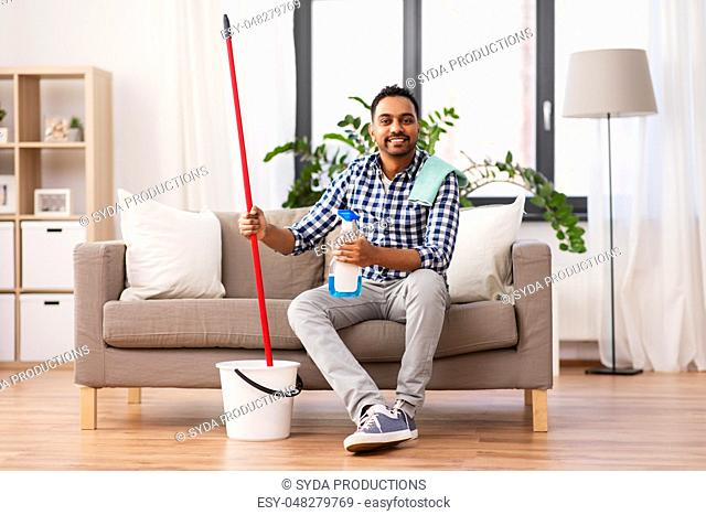 indian man with mop and detergent cleaning at home