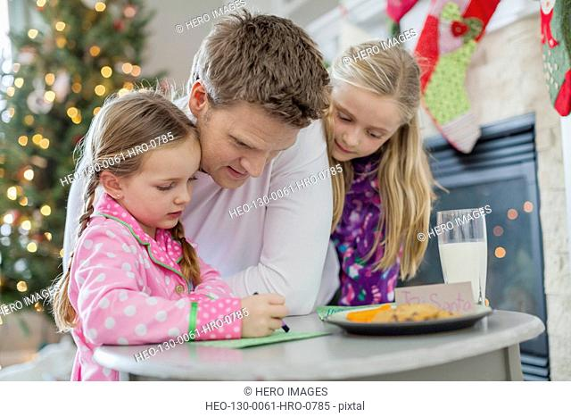 Family writing letter to Santa at table