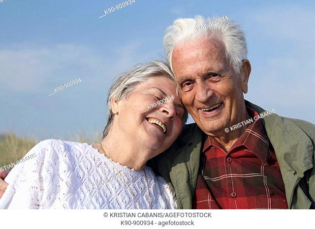 Head and shoulder photograph of elderly caucasian couple laughing and leaning to eachother while the senior man looking into the camera with blue sky