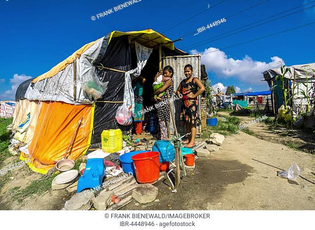 Two women, one carrying baby, standing in front of tent, camp for people who lost homes in 2015 earthquake, Boudha suburb, Kathmandu, Kathmandu District, Nepal