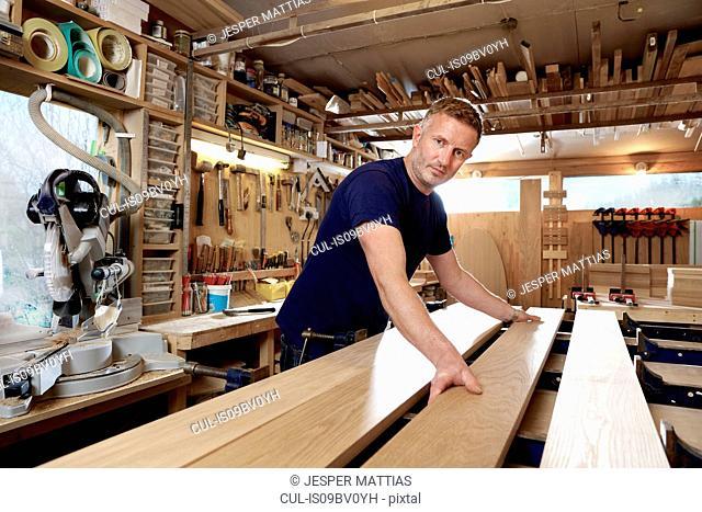 Craftsman preparing planks of wood in workshop