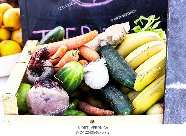 A wooden basket of different vegetables and fruits