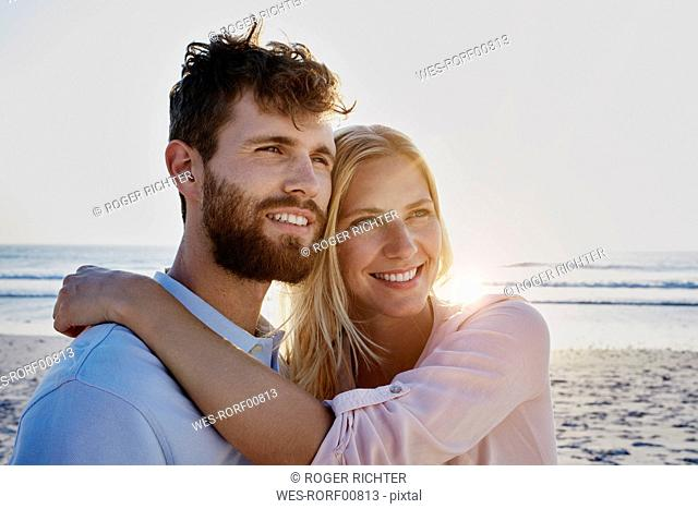 Smiling couple on the beach at sunset