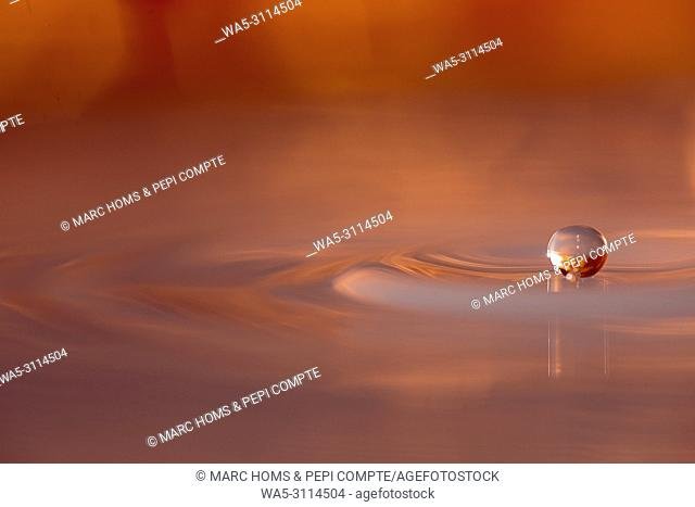 Copper colored water drop floting above the surface of the water