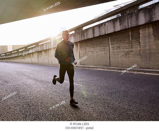 Male runner running on urban street into tunnel