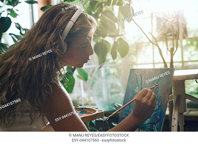 Indoor shot of professional female artist with headphones painting on canvas in studio with plants
