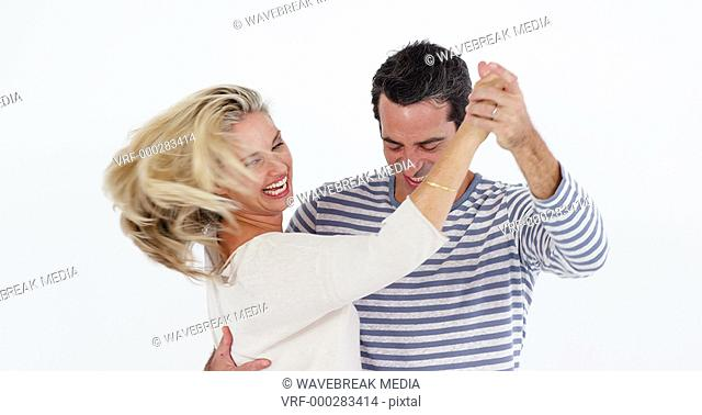 Mature couple dancing against white background