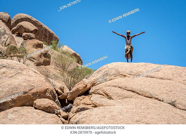 At the Damara Living Museum, a male tribe member stands on top of a large rock with his arms outstretched. The Living Museum is located north of Twyfelfontein