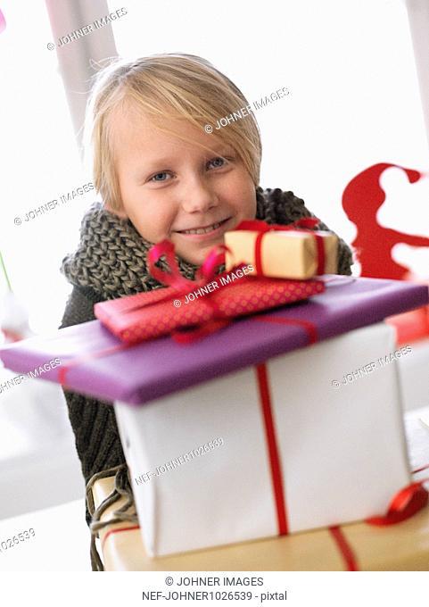 Sweden, Stockholm, girl behind stack of christmas gifts