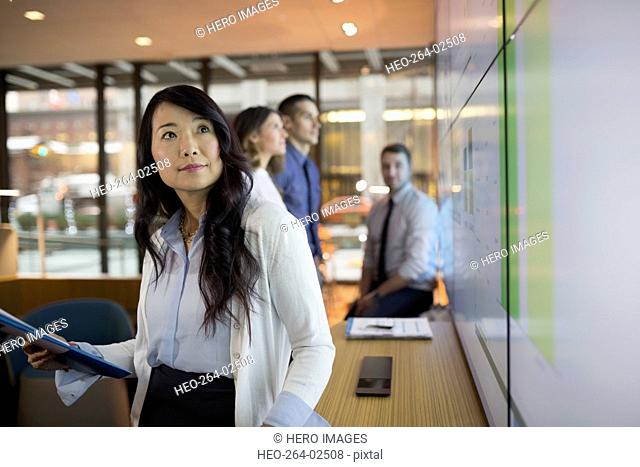 Businesswoman looking up projection screen in conference room