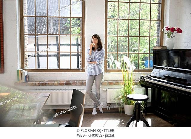 Woman standing at window of her loft apartment, drinking coffee