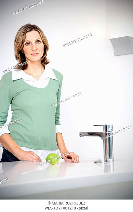 Portrait of woman standing in a modern kitchen