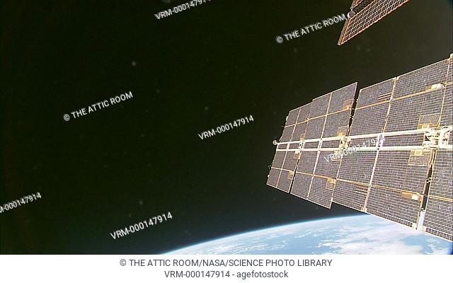 View from one of the International Space Station windows dominated by a large solar panel - tilted towards the Sunlight. The edge of the Earth can be seen below