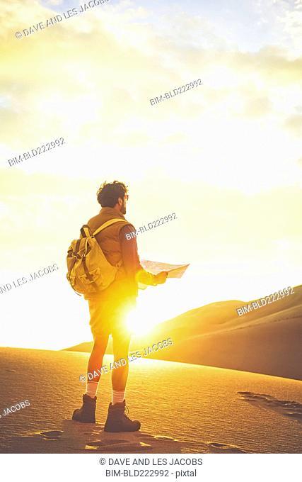 Hispanic man hiking on sand dune using map