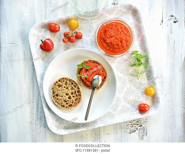 Ajvar in a jar and on half a bread roll
