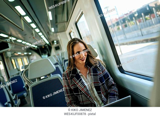 Businesswoman on a train using a laptop