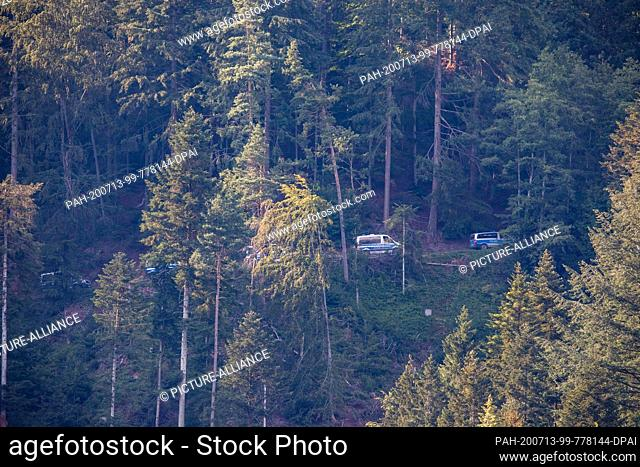 13 July 2020, Baden-Wuerttemberg, Oppenau: Police vehicles drive through the forest near Oppenau. With a large contingent