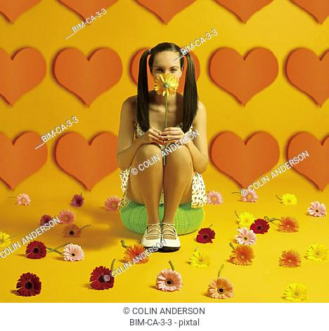 Woman sitting holding flower