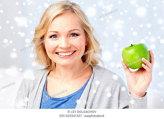 healthy eating, organic food, fruits, diet and people concept - happy middle aged woman with green apple at home over snow
