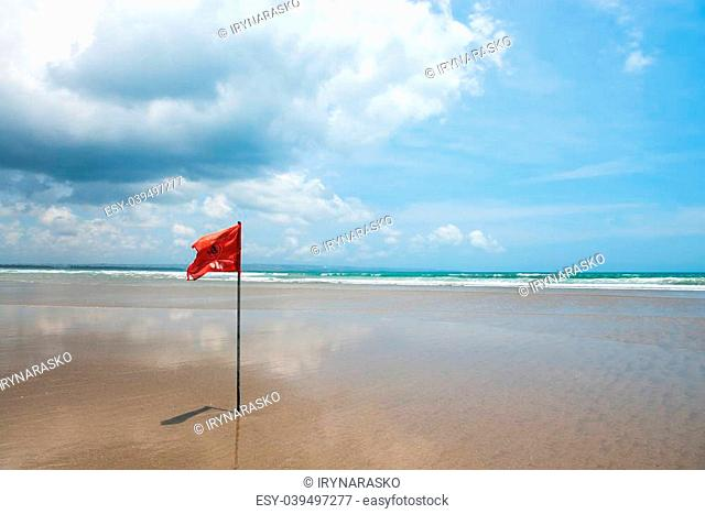 Red flag on beach with no swimming notes. Season of storms and strong currents