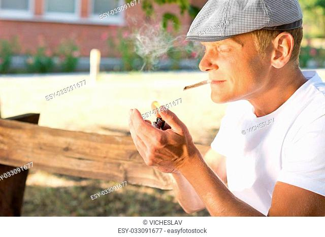 Man sitting in a park lighting up a cannabis joint clenched between his teeth with his lighter with copyspace