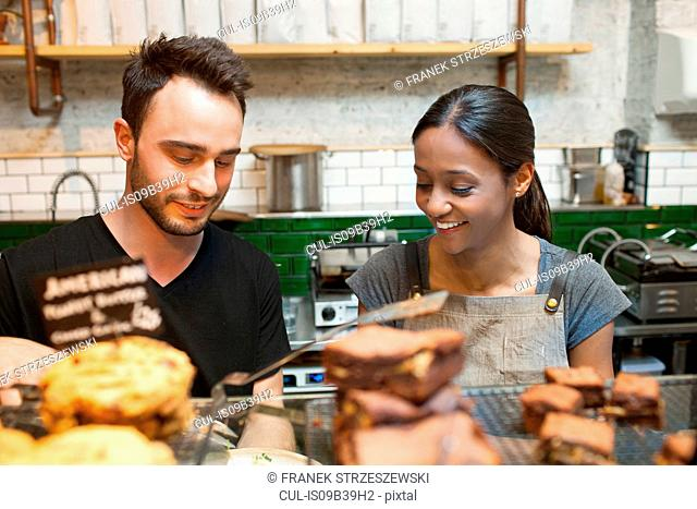 Waiter and waitress preparing food in cafe