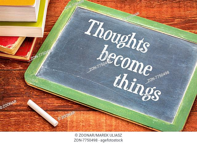 thoughts become things - law of attraction concept - inspirational text on a slate blackboard with a white chalk and a stack of books against rustic wooden...