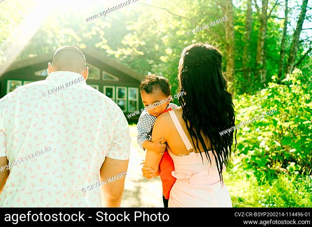 View from behind of a young family walking together on a summer's day