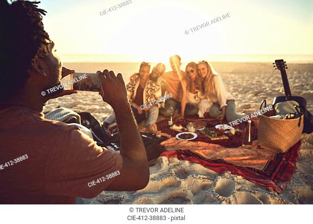 Young man with camera phone photographing friends enjoying picnic on sunny summer beach