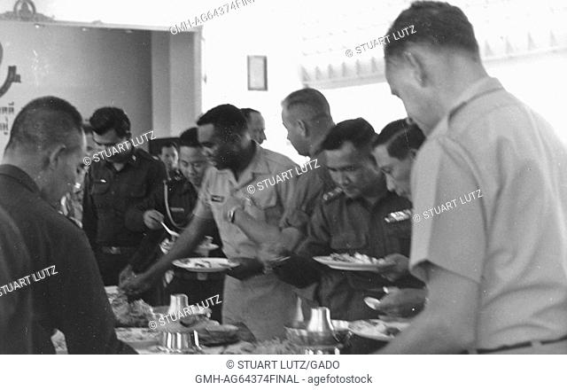 Lieutenant AL Walker, center, serving himself food from a buffet, surrounded by American and Vietnamese soldiers, also serving themselves food, Vietnam, 1964