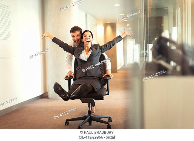 Playful businessman pushing exuberant businesswoman down corridor in office chair