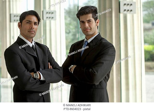India, Two businessmen in suits standing side by side with arms folded
