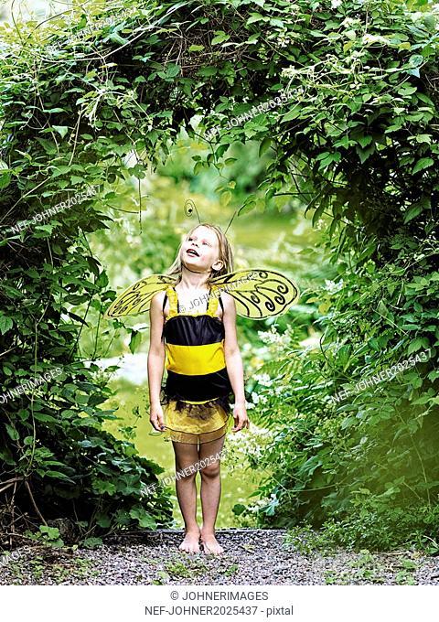Girl in garden wearing bee costume
